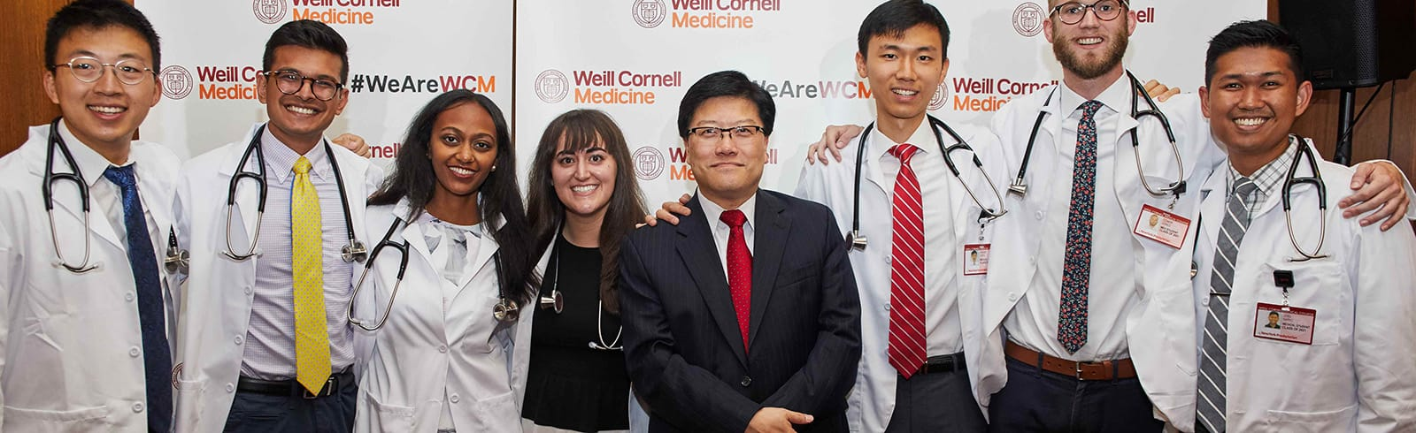 Dean Choi standing with students in white coats.