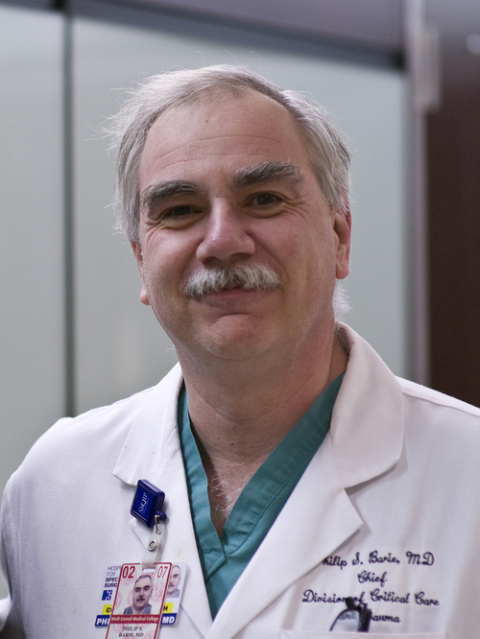 a man smiling for a portrait in a white coat